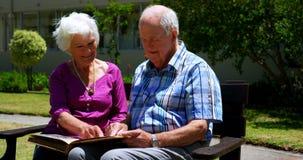 Vista delantera de los pares mayores caucásicos activos que miran el álbum de foto en el jardín de la clínica de reposo 4k metrajes