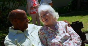 Vista delantera de los pares mayores de la raza mixta activa que sonríen y que miran uno a en el jardín del nur almacen de video