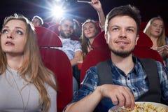 Vista delantera de los pares que comen las palomitas en cine imagenes de archivo