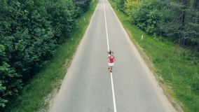 Vista delantera de parte delantera superior de una mujer joven apuesta que corre a lo largo de la autopista en la antena del bosq metrajes