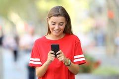 Vista delantera de un adolescente usando un teléfono elegante Foto de archivo