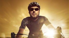 Vista delantera de un ciclista que compite con durante puesta del sol Imagenes de archivo