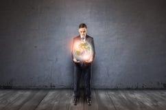 Vista delantera de un hombre de negocios que sostiene la tierra que brilla intensamente en sus brazos Foto de archivo libre de regalías