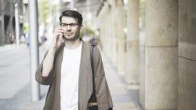 Vista delantera de un hombre de negocios hermoso usando su teléfono elegante en la calle Fotos de archivo libres de regalías