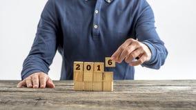 Vista delantera de un hombre que monta una muestra 2016 con los cubos de madera Imagen de archivo
