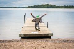Vista delantera de un muchacho joven que corre en un embarcadero y saltos en aire hacia una playa fotografía de archivo libre de regalías