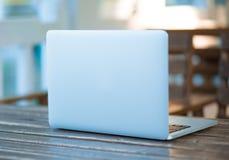 Vista delantera de un ordenador portátil en la tabla en una cafetería, balcón foto de archivo
