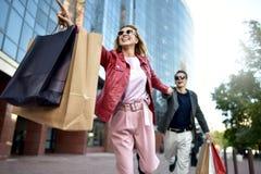 Vista delantera de un par casual de los compradores que corren en la calle hacia la cámara que sostiene los panieres coloridos foto de archivo libre de regalías