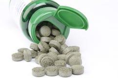 Vista delantera de una botella verde y de las píldoras de la vitamina Imagen de archivo