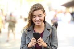 Vista delantera de una charla adolescente en un teléfono móvil Imágenes de archivo libres de regalías