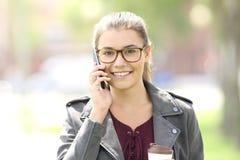 Vista delantera de una muchacha de la moda que habla en el teléfono Imágenes de archivo libres de regalías