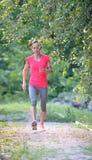 Vista delantera de una muchacha del corredor que lleva el funcionamiento colorido de la ropa de deportes Foto de archivo libre de regalías