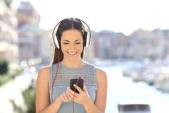 Vista delantera de una muchacha que escucha la m?sica que elige canciones fotografía de archivo libre de regalías