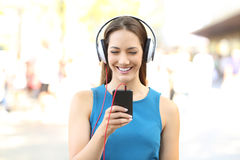 Vista delantera de una muchacha que escucha la música en la calle Imagen de archivo