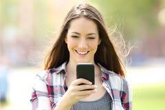 Vista delantera de una muchacha que usa un teléfono elegante Fotos de archivo libres de regalías