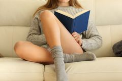 Vista delantera de una mujer con las piernas perfectas que lee un libro imagen de archivo