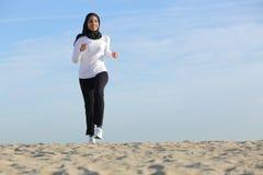 Vista delantera de una mujer de los emiratos del saudí del árabe que corre en la playa Foto de archivo