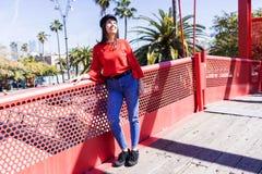 Vista delantera de una mujer joven hermosa que lleva la ropa urbana que se inclina en una cerca metálica del puente mientras que  imagenes de archivo