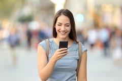 Vista delantera de una mujer que usa un teléfono elegante en la calle Imágenes de archivo libres de regalías
