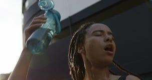 Vista delantera del agua de colada de la mujer afroamericana joven en su cabeza en la ciudad 4k metrajes
