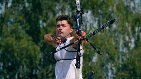 Vista delantera del arquero de sexo masculino mientras que apunta Tiroteo con un arco y las flechas en tiro al arco almacen de metraje de vídeo