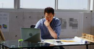 Vista delantera del arquitecto de sexo masculino asiático que usa el ordenador portátil en el escritorio en una oficina moderna 4 metrajes