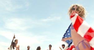 Vista delantera del baile caucásico de la mujer con la bandera americana en la playa 4k metrajes