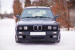 Vista delantera del coche familiar viejo, negro, alemán en invierno Fotografía de archivo