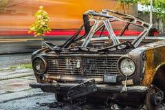 Vista delantera del coche quemado en el camino con tráfico de coche en un fondo Fotos de archivo libres de regalías