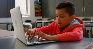 Vista delantera del colegial asiático atento que estudia con el ordenador portátil en sala de clase en la escuela 4k metrajes