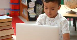 Vista delantera del colegial asiático atento que estudia con el ordenador portátil en una sala de clase en la escuela 4k almacen de video