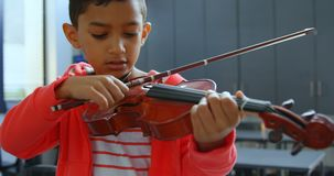 Vista delantera del colegial asiático atento que toca el violín en sala de clase en la escuela 4k almacen de metraje de vídeo