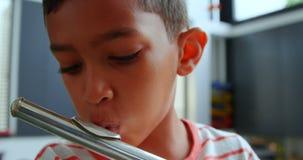 Vista delantera del colegial asiático atento que toca la flauta en sala de clase en la escuela 4k almacen de video