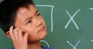 Vista delantera del colegial asiático pensativo que rasguña su cabeza contra la pizarra en la sala de clase 4k almacen de video