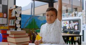 Vista delantera del colegial asiático que aumenta la mano mientras que estudia en el escritorio en sala de clase en la escuela 4k metrajes
