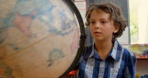 Vista delantera del colegial caucásico que estudia el globo en el escritorio en sala de clase en la escuela 4k almacen de metraje de vídeo