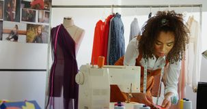 Vista delantera del diseñador de moda de sexo femenino afroamericano que mira muestras del paño en el taller 4k almacen de video
