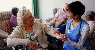 Vista delantera del doctor de sexo femenino asiático que obra recíprocamente con la mujer mayor en la clínica de reposo 4k almacen de video