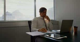 Vista delantera del ejecutivo de sexo masculino caucásico joven que trabaja en el ordenador portátil en el escritorio en una ofic almacen de video