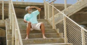 Vista delantera del hombre afroamericano mayor activo con proteger el ojo que se sienta en la escalera en la 'promenade' 4k almacen de video