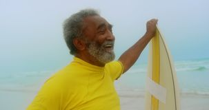Vista delantera del hombre afroamericano mayor activo feliz con la tabla hawaiana que se coloca en la playa 4k almacen de metraje de vídeo