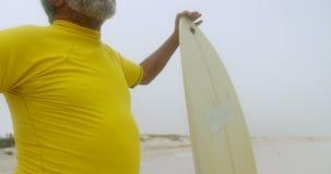 Vista delantera del hombre afroamericano mayor activo pensativo con la tabla hawaiana que se coloca en la playa 4k almacen de metraje de vídeo
