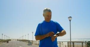 Vista delantera del hombre caucásico mayor activo usando smartwatch en una 'promenade' en la playa 4k almacen de metraje de vídeo
