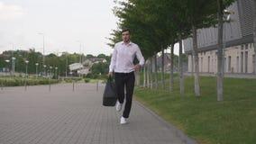 Vista delantera del hombre de negocios elegante hermoso en la camisa blanca que corre con la maleta grande en a cámara lenta Fond metrajes
