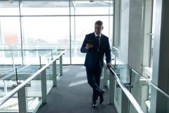 Vista delantera del hombre de negocios inclinada en la verja y usar su teléfono móvil foto de archivo