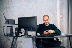 Vista delantera del hombre de negocios joven usando el teléfono móvil en oficina Fotos de archivo libres de regalías