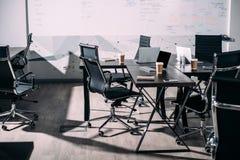 vista delantera del interior de la oficina moderna con las sillas, tazas de papel de café, ordenadores portátiles imagen de archivo libre de regalías