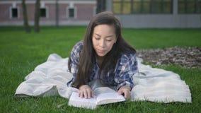 Vista delantera del modelo asiático feliz de la muchacha del estudiante con el pelo oscuro que hace la investigación en el área d metrajes