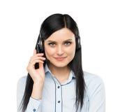 Vista delantera del operador moreno sonriente del teléfono de la ayuda con las auriculares Imagen de archivo