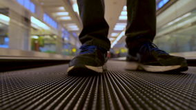 Vista delantera del primer sobre el viajero de las piernas del hombre que usa la escalera móvil plana móvil en el terminal de aer